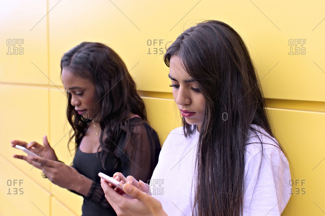 Two friends of different races chatting on their smartphones