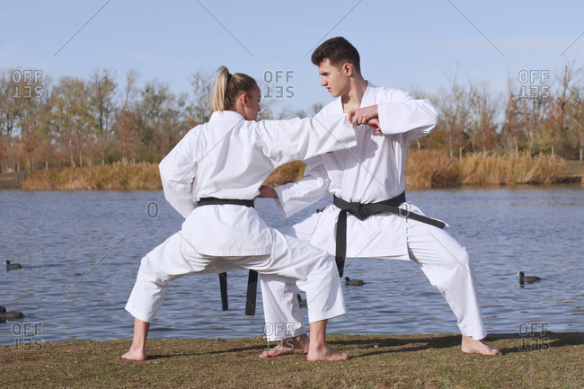 Young girl and young boy karate experts practice and fight by the water