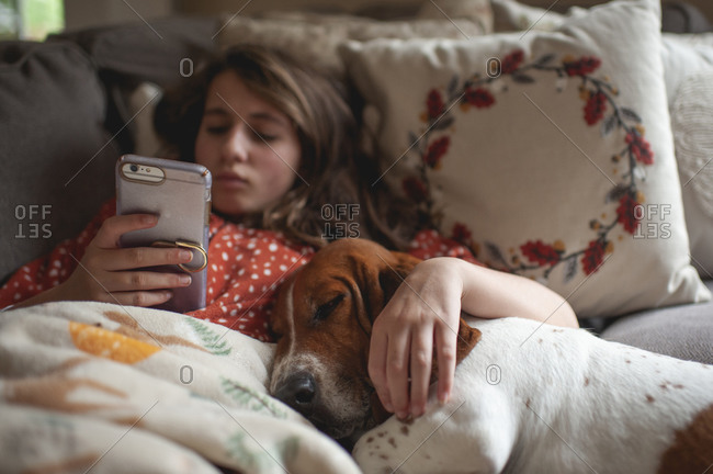 Tween girl looking at her phone while cuddling with hound dog on couch