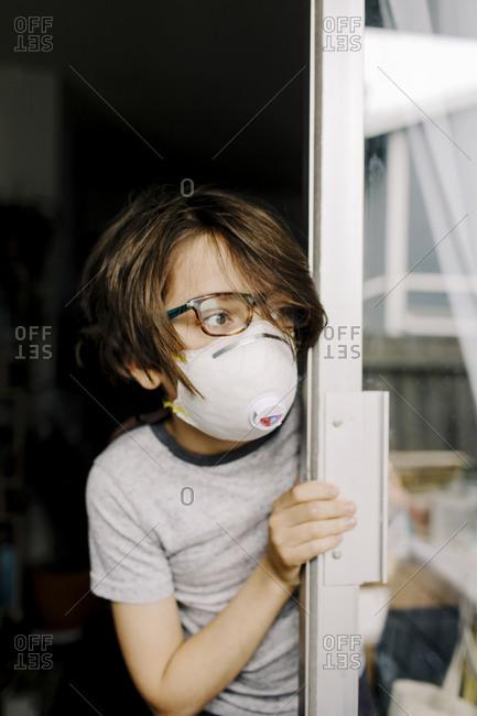 Boy wearing mask looking through window