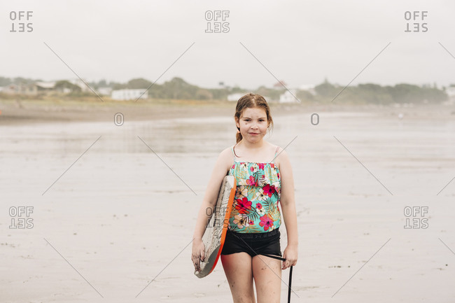Closeup of a young girl holding a boogie board on the beach