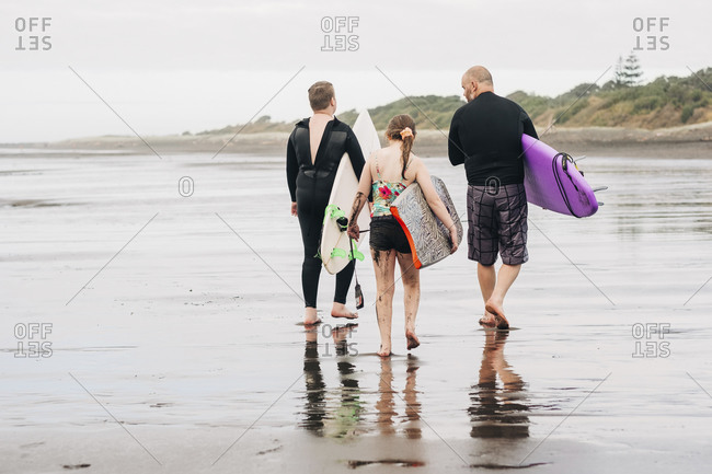 Family walking down the beach with boogie and surf boards