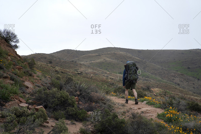 Man walks a rugged trail in the Superstition Mountains of Arizona