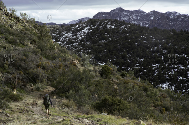 Man hiking mountainous trail with patchy snow covered mountains