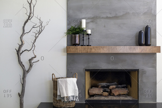Modern gray textured fireplace with basket and tree branch