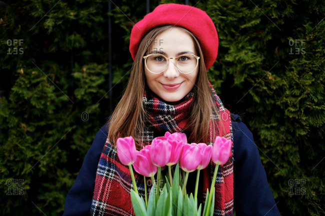 Young French millennial girl in beret and coat with tulips in hands
