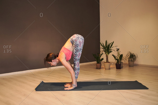 Young woman doing yoga on yoga mat in atmospheric yoga studio