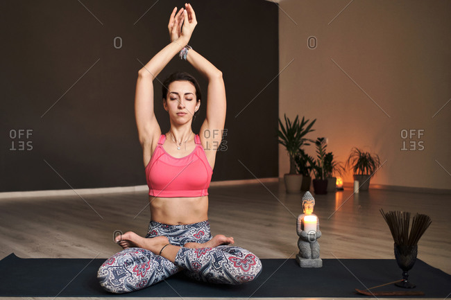 Young woman meditating alone with a yoga studio