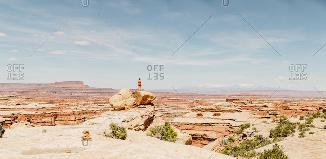 Panorama of a hiker standing on rock looking out over The Maze in Utah