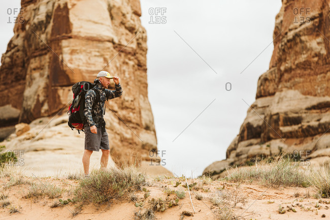 Hiker with big backpack pauses under red rock structures in Utah