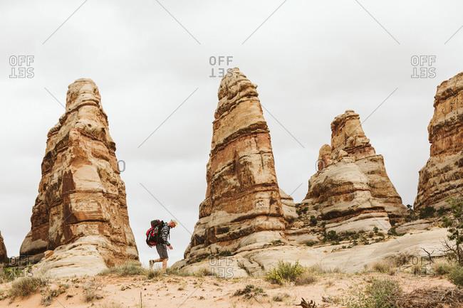 Male hiker walks next to red rocks towers in the desert of Utah