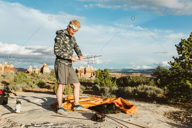 Stylish male camper sets up tent in the deserts of Utah