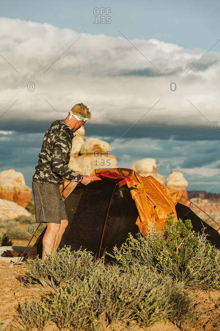 Man in camo jacket sets up tent at sunset in the desert of Utah