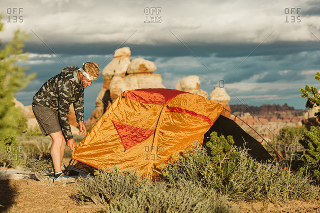 Camper in camo windbreaker finishes setting up tent in Utah desert