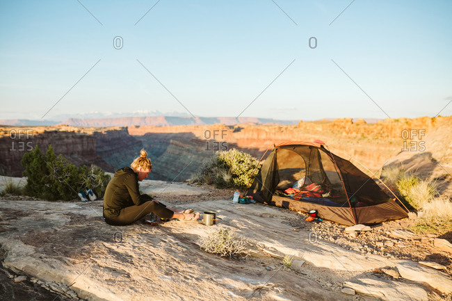 Female camper prepares food next to campsite overlooking grand canyon