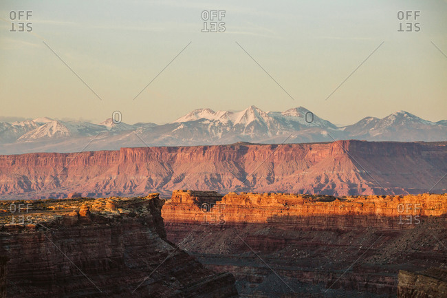 Last light on canyon walls in Utah desert with la sal mountains behind