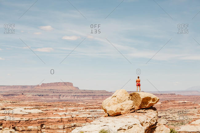 Strong woman looks over the maze Utah on sunny desert day