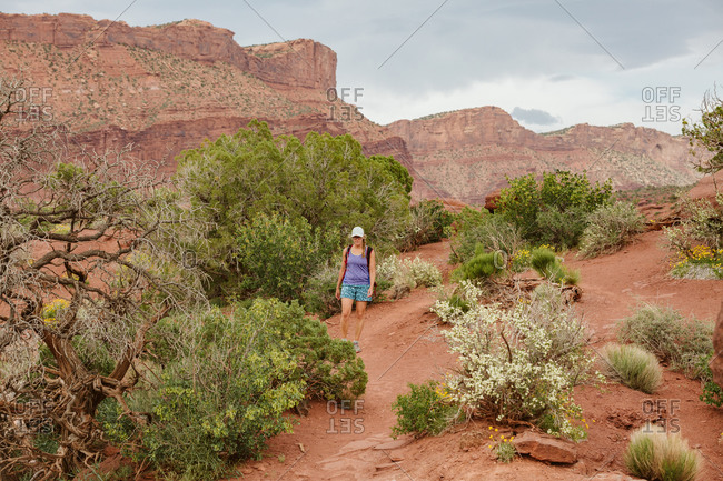 Hiker walks on red dirt path amongst desert plants near Moab Utah