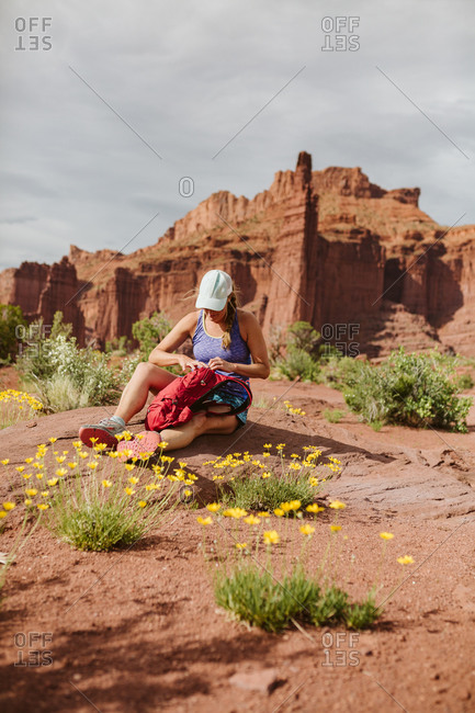Female hiker sits down in yellow flowers at fisher towers Moab Utah