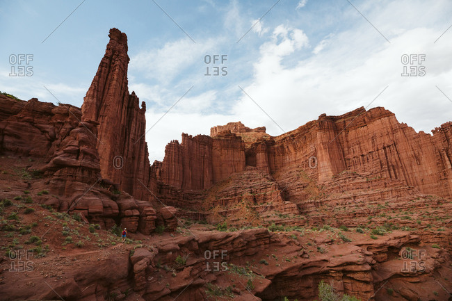 Lone hiker under the red rock formation of fisher tower near Moab