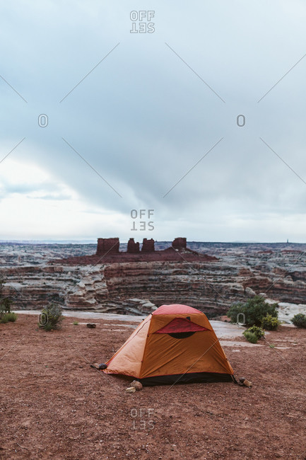 Orange tent held down by rocks at campsite in the maze Utah