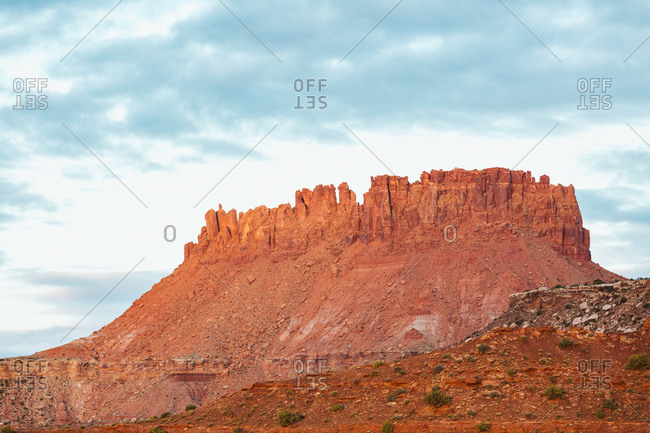 Morning light turns red rock sandstone butte golden in canyonlands