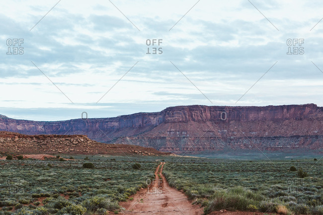 Straight red two track dirt road headed off to nowhere in Utah desert