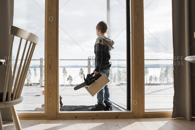Boy playing with toy tools at his home overlooking the sea