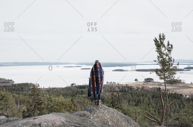Woman wrapped in a blanket looking at the view of the ocean and forest