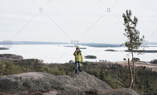 Young boy posing for a photo on a rock with a beautiful view behind