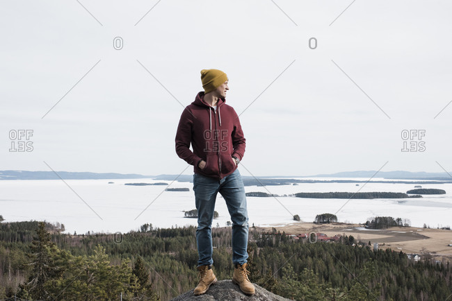 Man standing on a rock whilst hiking a hill above the ocean in Sweden