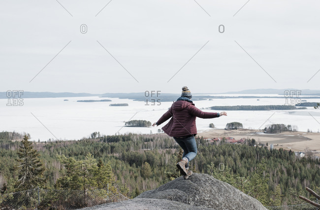 Woman jumping rocks whilst hiking up a mountain in Sweden