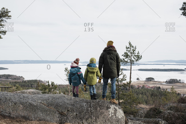 Father and his kids enjoying a beautiful coastal view in Sweden