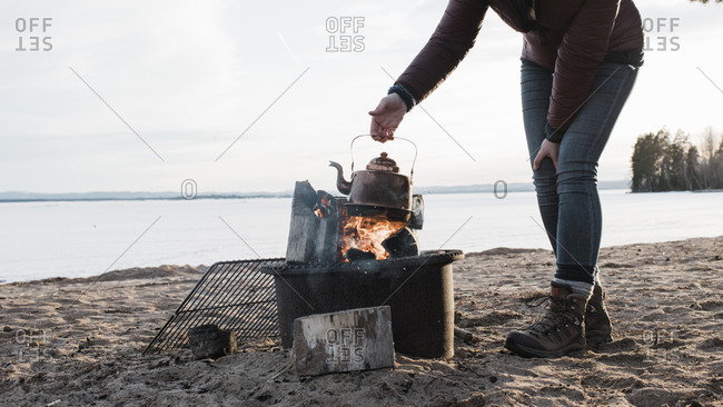Woman holding a kettle over a camp fire at the beach in Sweden