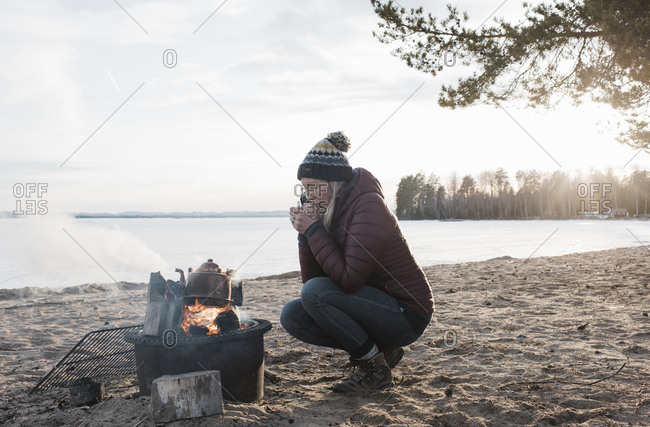 Woman warming up sat next to a camp fire on an empty beach in Sweden