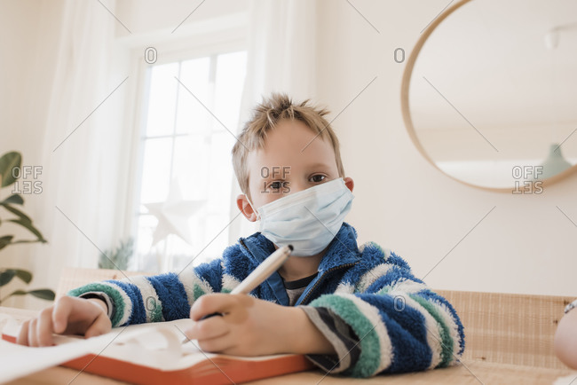Boy home schooling with a medical mask on to protect from a virus