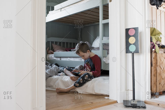 Boy sitting in his bedroom playing computer games in his pajamas