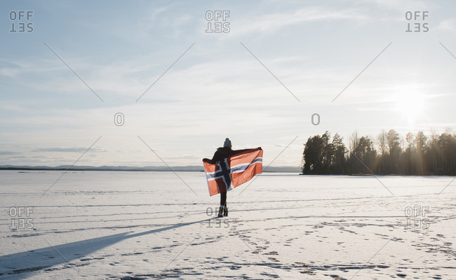 Woman walking across a frozen lake holding a Norwegian flag at sunset