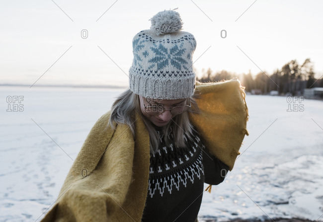 Portrait of woman holding scarf whilst walking on a frozen lake
