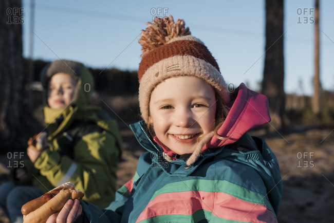Portrait of a young girl eating a hot dog by a campfire in Sweden