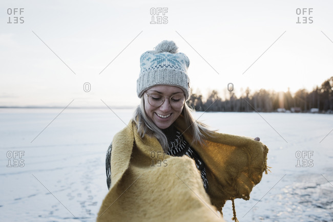 Woman smiling whilst walking on a frozen lake in winter in Sweden