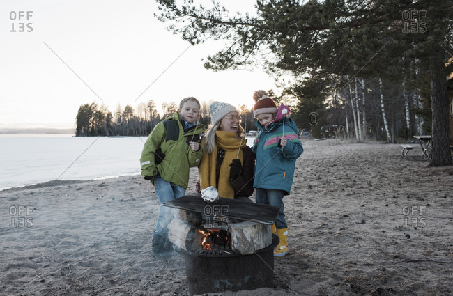 Mother and her kids eating marshmallows by a campfire at the beach