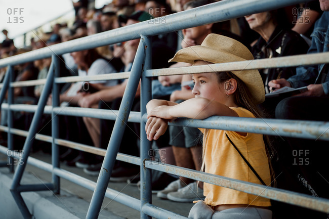 Little girl watching the rodeo with a cowboy hat on