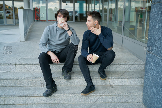 Front view of two young men talking sitting on a city staircase