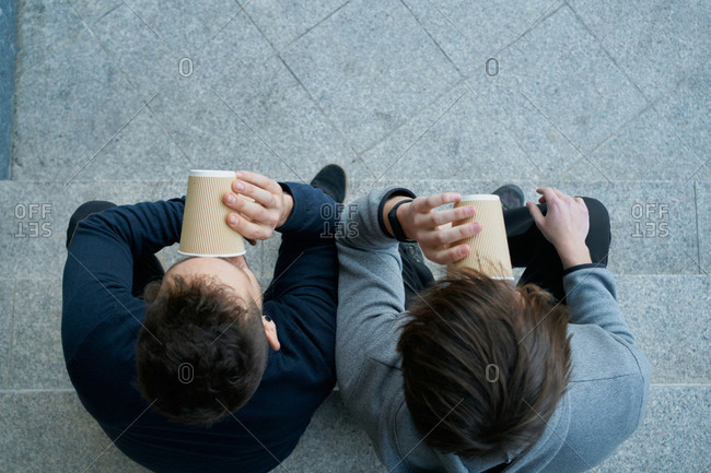 Top view of two young men sitting on a city staircase and drinking coffee