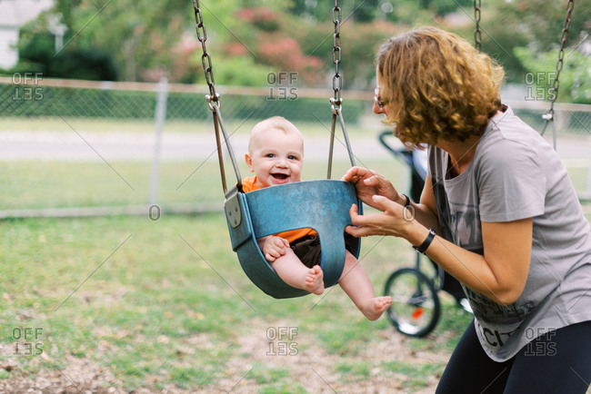 Little six month old boy and his grandma at the playground.