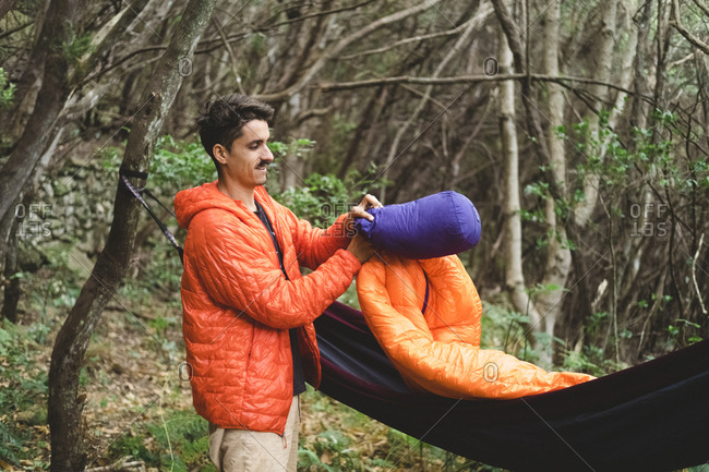 A man packs a sleeping bag and hammock at campsite in the forest