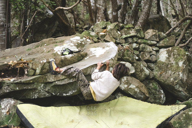 A young kid climbs a rock in a forest