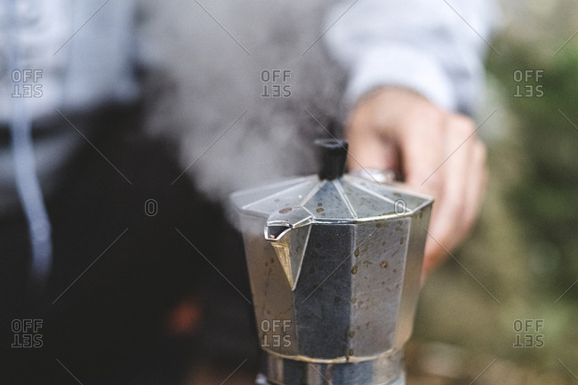 Close up of a man preparing coffee outdoors