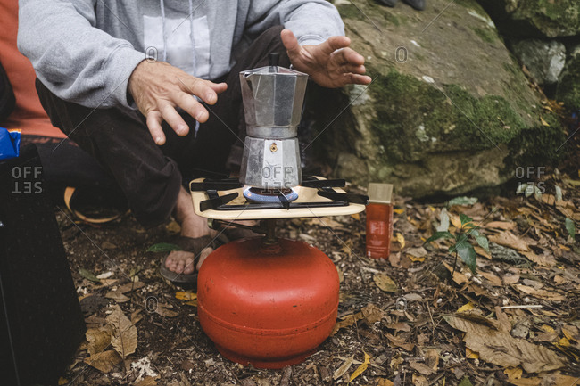 Lower part of a man preparing coffee outdoors